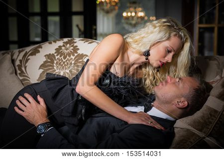 Woman in fancy dress laying on top of man