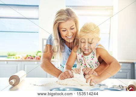 Adoring young mother teaching her daughter to bake as they stand together at the kitchen table kneading the dough for cookies