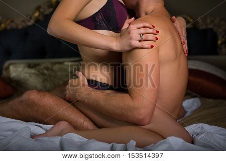 Couple in bedroom having foreplay before making love