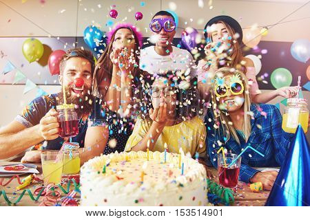 Group of six male and female festive partygoers in front of large white frosting covered cake surrounded by confetti in room