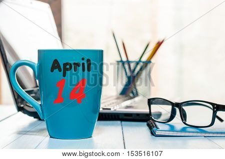 April 14th. Day 14 of month, calendar on business office background, workplace with laptop and glasses. Spring time, empty space for text.