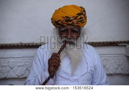JODHPUR, RAJASTHAN, INDIA - FEBRUARY 10, 2016 - Portrait of an unidentified indian man smoking opium from a pipe inside Jodhpur fort