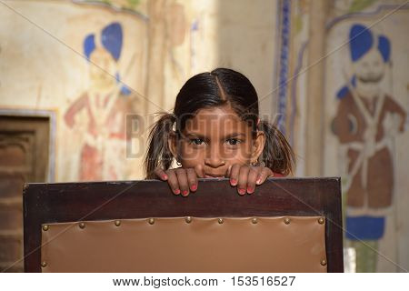 MANDAWA, RAJASTHAN, INDIA - FEBRUARY 14, 2016 - Portrait of an unidentified indian child looking at the camera behind a chair inside the courtyard of a traditional haveli