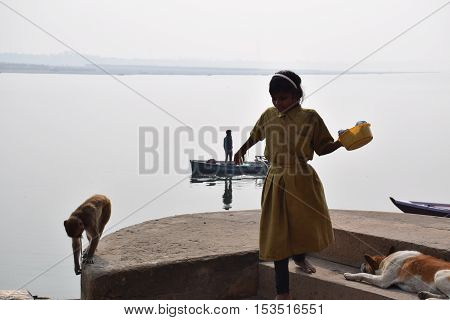 VARANASI, UTTAR PRADESH, INDIA - FEBRUARY 17, 2016 - Unidentified indian kid walking on the ghats in Varanasi with a monkey following her and holy river Ganga on the background