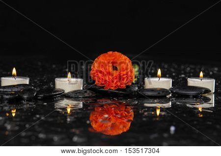 Spa still life with  ranunculus and three candle on pebbles