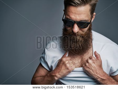 Single long bearded man in sunglasses showing off his chest by pulling down white shirt collar over gray background