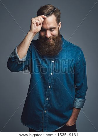Well groomed handsome bearded man in blue denim shirt looking downward with happy expression while combing his hair over gray background