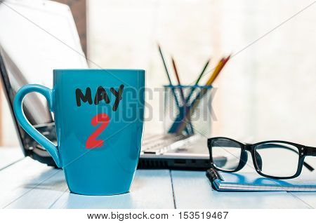 May 2nd. Day 2 of month, calendar on morning coffee cup, business office background, workplace with laptop and glasses. Spring time, empty space for text.