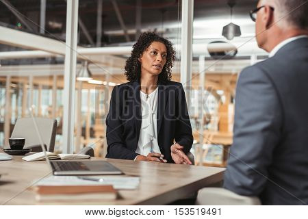 Mature businessman and young work colleague discussing business while sitting together at a table in an office boardroom