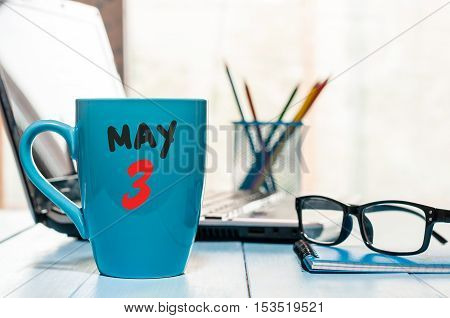 May 3rd. Day 3 of month, calendar on morning coffee cup, business office background, workplace with laptop and glasses. Spring time, empty space for text.