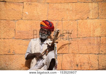 JAISALMER, RAJASTHAN, INDIA - FEBRUARY 10, 2016 - Portrait of an unidentified aged indian man with white beard playing a traditional string instrument outside Jaisalmer fort
