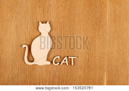 Wooden silhouette of a cat on a wooden surface. Background