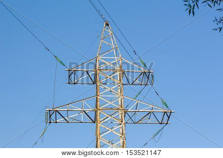 High voltage line tower against the blue sky