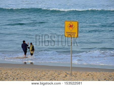 Sydney Australia - Jun 9 2013. A sign reads Dangerous currents. Swimming is forbidden.