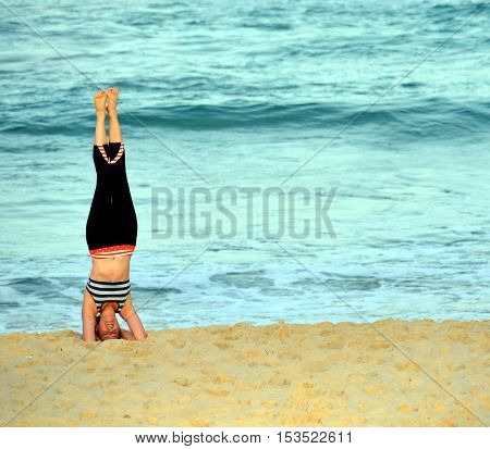 Sydney Australia - Jun 9 2013. Woman standing on her head and doing yoga on the beach. Woman practices Ashtanga Vinyasa yoga Surya Namaskar Sun Salutation asana Urdhva Mukha Svanasana
