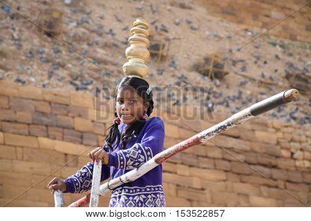 JAISALMER, RAJASTHAN, INDIA - FEBRUARY 10, 2016 - Portrait of an unidentified indian baby acrobat performing outside Jaisalmer fort