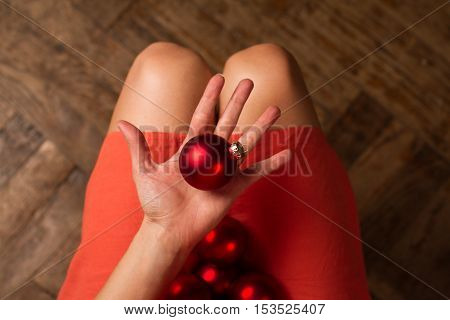 horizontal top view of woman holding Christmas red decoration globes on her lap and one in her hand