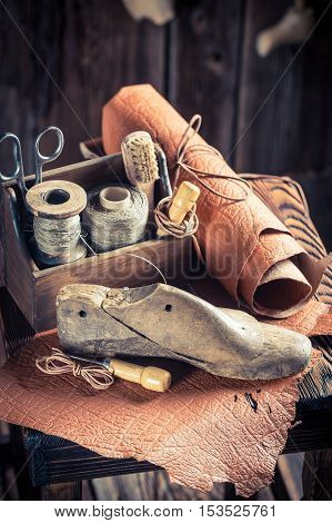 Small Shoemaker Workshop With Tools, Leather And Shoes