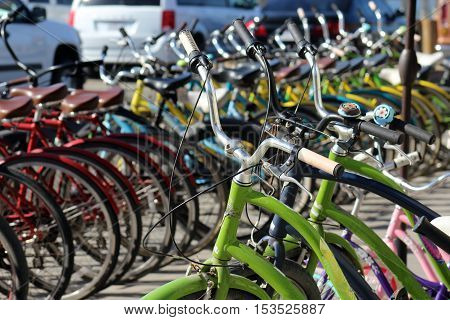 Bright colored beach cruiser bicycles lined up outdoors for customers to rent in Venice Beach, California.