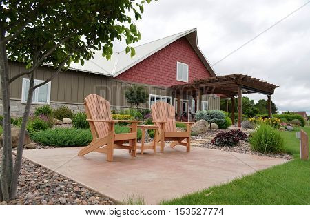 Two Adirondack chairs on a patio in the gardens