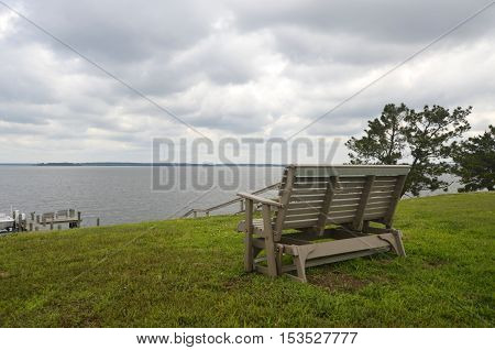 Glider style bench on a green grassy knoll overlooking a large body of water on an overcast summer day