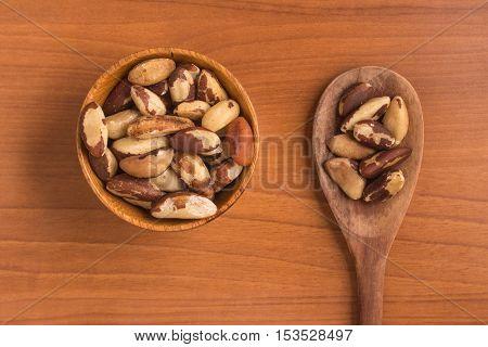 Brazilian Nuts into a bowl. Castanha do Para over a wooden table