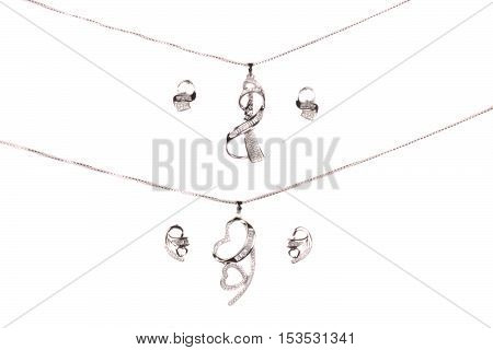 Two sets of silver jewelery beautifully designed with small gemstones on white studio background