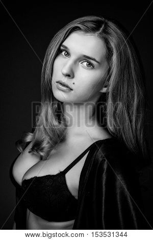 Beautiful sexy blond woman with big breasts in black lingerie. Big boobs, slim body. black and white photo