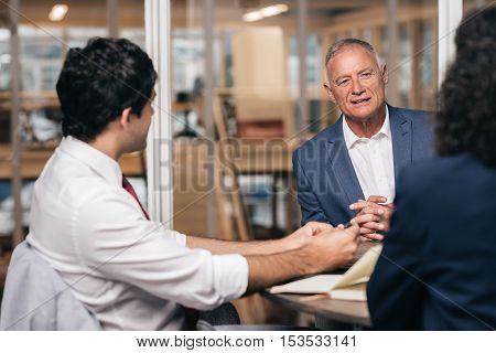 Mature businessman talking with young staff members while sitting together at a table in an office boardroom