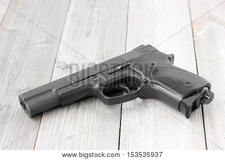 Pneumatic (gas) gun on a wooden table top view.