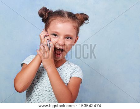 Excited Kid Girl Talking On Mobile Phone With Opened Mouth On Blue Background With Empty Copy Space.