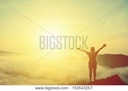 Silhouette of woman praying over sea of mist over mountain for background