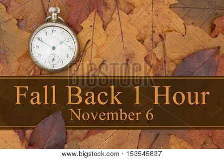 Daylight Savings Time message Some fall leaves and retro pocket watch with text Fall Back 1 Hour November 6