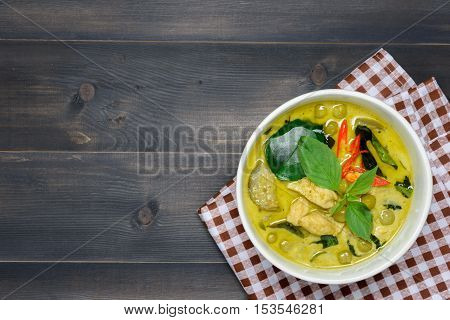 green curry with chicken (Kang Keaw Wan Gai) with brown tablecloth on wooden background top view Thai local food