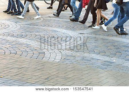 set of feet of people walking on the sidewalk