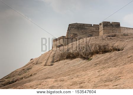 Dindigul India - October 23 2013: Brown-beige boulder with the ramparts of the historic Dindigul Rock fort under light blue sky. Brown-beige as dominant color.