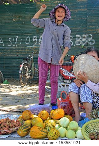 Vinh, Vietnam - May 29, 2015: woman is selling fruits and vegetables outdoor in Vinh, Vietnam