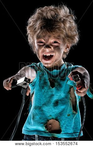 Boy has a electric shock. Portrait of funny little electrician with cord plug over black background. Electricity power concept.
