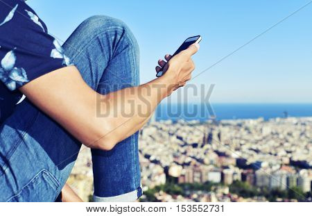closeup of a young caucasian man using his smartphone in the top of a hill in Barcelona, Spain, with a panoramic view of the city from above