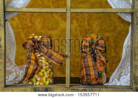two glass jars with orange ribbon full of Halloween candy on window sill through rustic window with lace curtains