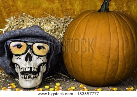 Halloween skull with 3D glasses and wool cap on burlap and candy corn next to orange pumpkin straw bale and orange background