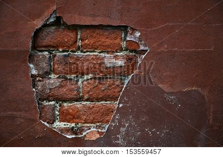 Weathered stained brick wall with cracked cement tension