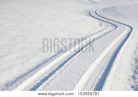 Car tire track on a empty winter road