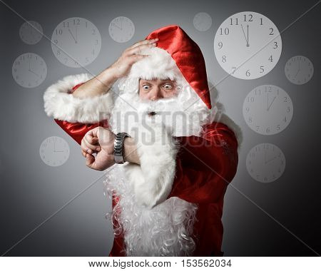 Santa Claus is looking at his wristwatch. Time and Concept of being late.