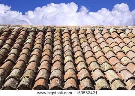 Old roof tiles blue sky and clouds in the background