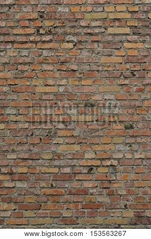 Weathered stained old brick wall background. Texture of an old wall of several floors with lots of rows of bricks