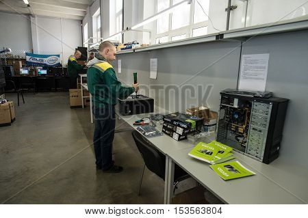 Saint-Petersburg Russia - October 19 2016: The production line of a small business computer assembly. Engineer a production line with a screwdriver in his hands