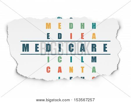 Medicine concept: Painted blue word Medicare in solving Crossword Puzzle on Torn Paper background