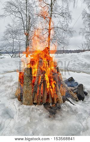 Outdoor bonfire in winter in the middle of snow forest