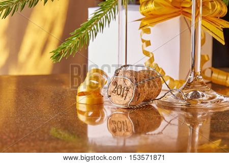 Two glasses with champange, fir tree branch, gift box on a gold background. New year and Christmas.